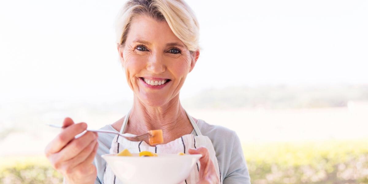 Una donna in menopausa mangia un'insalata di frutta